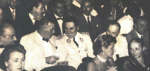 El presidente Perón escucha divertio algún comentario del Sr. Carlos Aloé. A sus costados, el ministro de Relaciones Exteriores Dr. Remorino y el Sr. Apold intentan consustanciarse con el militar